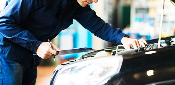 Mechanic-With-Clipboard-Examining-Car